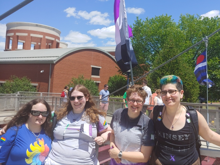 Four people pose outdoors in front of an ace flag. There is a leather flag in the background.