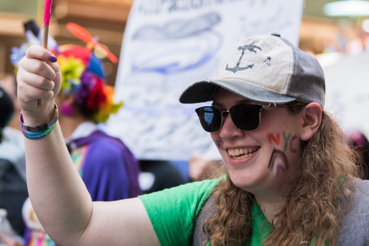 A person wearing a baseball hat and a green shirt with facepaint that says NYC over a rainbow in ace flag colors.