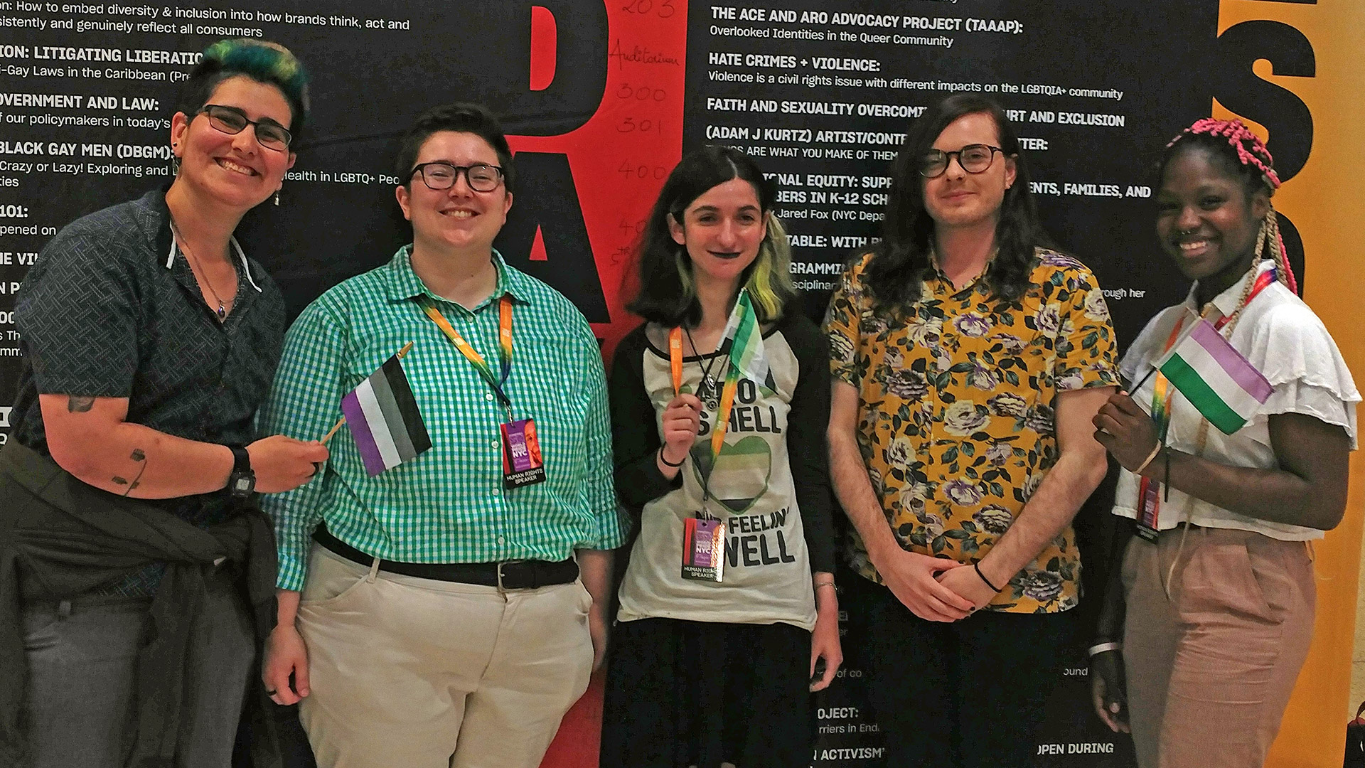 Five people standing in front of the conference schedule poster, holding the asexual, aromantic, and genderqueer flags.